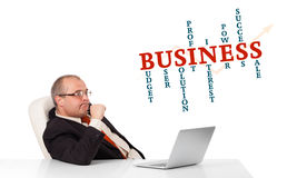 Bisinessman sitting at desk and looking laptop with business wor Stock Photography