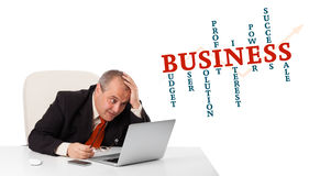 Bisinessman sitting at desk and looking laptop with business wor Stock Photos