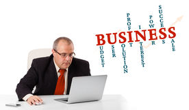 Bisinessman sitting at desk and looking laptop with business wor Royalty Free Stock Image