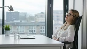 Bisinesswoman Sitting and Using a Laptop Indoors royalty free stock image