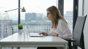 Bisinesswoman Sitting and Using a Laptop Indoors stock video footage