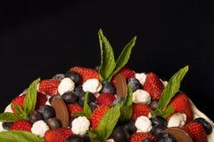 Biskwitowy domowej roboty tort z śmietanką i jagodami na czarnym tle Fotografia Stock
