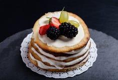 Biskwitowy domowej roboty tort z śmietanką i jagodami na czarnym tle Obraz Stock