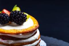 Biskwitowy domowej roboty tort z śmietanką i jagodami na czarnym tle Obrazy Stock