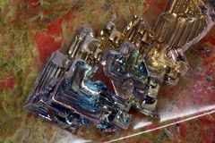 Bismuth crystal on a unakite stone stock photo