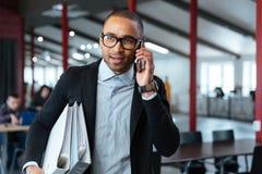 Bisnessman运载的文件夹和谈话在电话 免版税库存照片