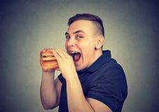 Bisogno mangiatore di uomini un hamburger saporito fotografia stock libera da diritti