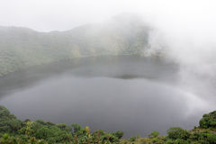 Bisoke crater lake in the mist. Rwanda: Mount Bisoke, also Visoke, is an extinct volcano in the Virunga Mountains of the Great Rift Valley. It straddles the Royalty Free Stock Image