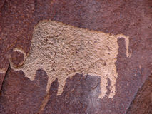 Bison petroglyph. Anasazi petroglyph of bison on reddish brown sandstone wall royalty free illustration