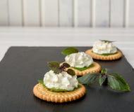 Bisquit薄脆饼干开胃菜用乳脂干酪和蓬蒿顶部 免版税图库摄影