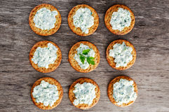 Bisquit cracker appetizers with cottage chees and parsley topping.  Stock Image
