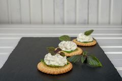Bisquit cracker appetizers with cream cheese and basil topping. On black stone background Royalty Free Stock Image