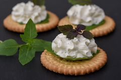 Bisquit cracker appetizers with cream cheese and basil topping. On black stone background Stock Photography