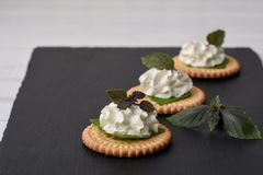 Bisquit cracker appetizers with cream cheese and basil topping. On black stone background Royalty Free Stock Photography