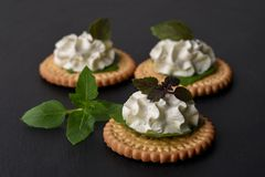 Bisquit cracker appetizers with cream cheese and basil topping. On black stone background Royalty Free Stock Photos