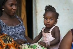 Portrait of a mother and her baby daughter at the Cupelon de Cima neighborhood in the city of Bissau. Bissau, Republic of Guinea-Bissau - January 31, 2018 royalty free stock photos