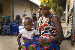 Portrait of a young mother and her baby daughter during a community meeting, at the Bissaque neighborhood in the city of Bissau. Bissau, Republic of Guinea Stock Photo