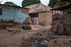 Children playing in front of their home, in a slum with an open air sewer, at in the city of Bissau royalty free stock image