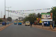 Street scene in the city of Bissau with people walking along an avenue, in Guinea-Bissau, West Africa Stock Photo