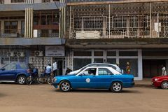 Street scene in the city of Bissau with a taxi and people in front of a crumbling building, in Guinea-Bissau stock photography
