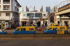 Street scene in the city of Bissau with people on a pedestrian overpass and public buses toca-toca, in Guinea-Bissa. Bissau, Republic of Guinea-Bissau - January Royalty Free Stock Images