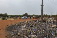 Bissau Republiken Guinea-Bissau - Februari 5, 2018: Folk som säljer kor nära en nedgrävning av sopor i utkanten av staden av Biss arkivfoto