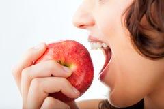 Bissen der jungen Frau in einem Apfel Lizenzfreie Stockfotos