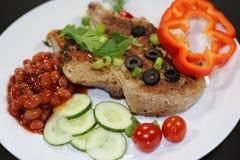 Bistecca al forno con il contorno di verdure su un fondo nero Fotografie Stock