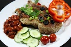 Bistecca al forno con il contorno di verdure su un fondo nero Immagine Stock