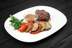 Bistecca arrostita con le verdure sul piatto bianco Fotografie Stock Libere da Diritti