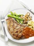 Bistecca arrostita con salsa al pomodoro e le verdure Fotografia Stock