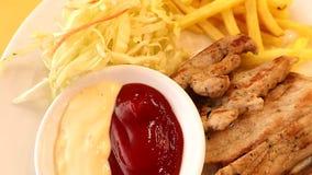 Bistecca arrostita della carne di maiale, pepe nero e primo piano delle fritture sul piatto bianco stock footage