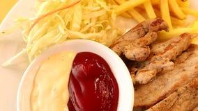 Bistecca arrostita della carne di maiale, pepe nero e primo piano delle fritture sul piatto bianco archivi video