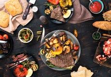 Bistecca arrostita e verdure arrostite sulla tavola di legno scura Fotografie Stock