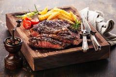 Bistecca arrostita rara media affettata Ribeye con le patate fritte Fotografie Stock