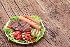 Bistecca arrostita, salsiccie e verdure. fotografie stock libere da diritti
