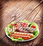 Bistecca arrostita, salsiccie e verdure. fotografie stock
