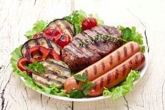 Bistecca arrostita, salsiccie e verdure. immagini stock libere da diritti
