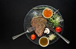 Bistecca arrostita Seasoned con gli utensili e la salsa fotografie stock libere da diritti