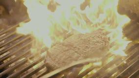 Bistecca che slitta sulla griglia con fuoco Mo lento video d archivio