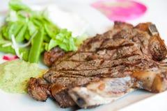 Bistecca con i contrassegni su una zolla bianca Fotografia Stock