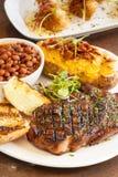 Bistecca con la patata al forno, i fagioli ed il pane all'aglio Immagini Stock Libere da Diritti