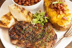 Bistecca con la patata al forno, i fagioli ed il pane all'aglio Immagine Stock Libera da Diritti