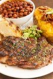 Bistecca con la patata al forno, i fagioli ed il pane all'aglio Fotografia Stock Libera da Diritti