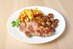 Bistecca con la vista laterale fritta dei funghi e delle patate fotografia stock libera da diritti