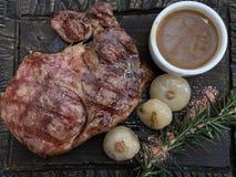 Bistecca con le cipolle, i rosmarini e la salsa su un bordo di legno immagine stock libera da diritti