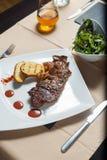 Bistecca con le patate arrostite con il lato dell'insalata Immagini Stock