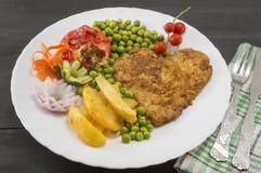 Bistecca con le patate, i pomodori ciliegia ed i piselli sul piatto immagine stock libera da diritti