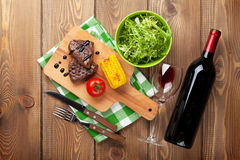 Bistecca con mais arrostito, insalata e vino rosso immagini stock