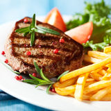 Bistecca cotta con le patate fritte Fotografie Stock